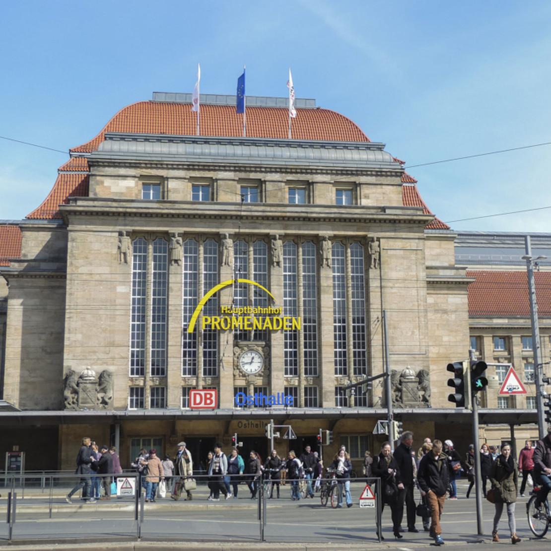 Fassade Westhalle Hauptbahnhof Leipzig mit Passanten.