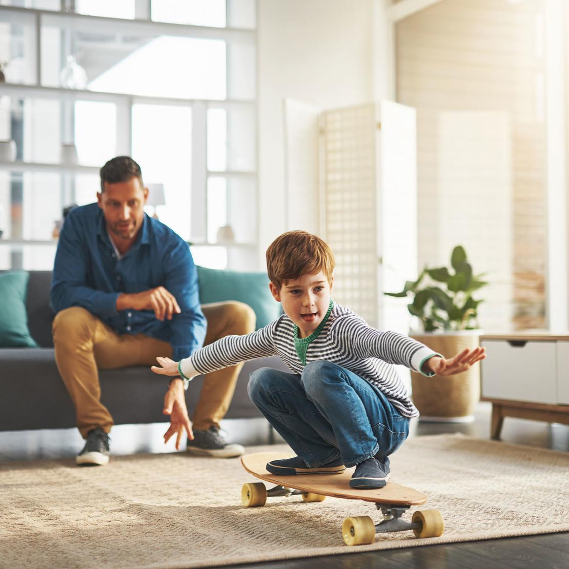 Fotografie eines Mannes in einer modernen Wohnung. Vor ihm macht ein Kind auf einem Skateboard Gleichgewichtsübungen.