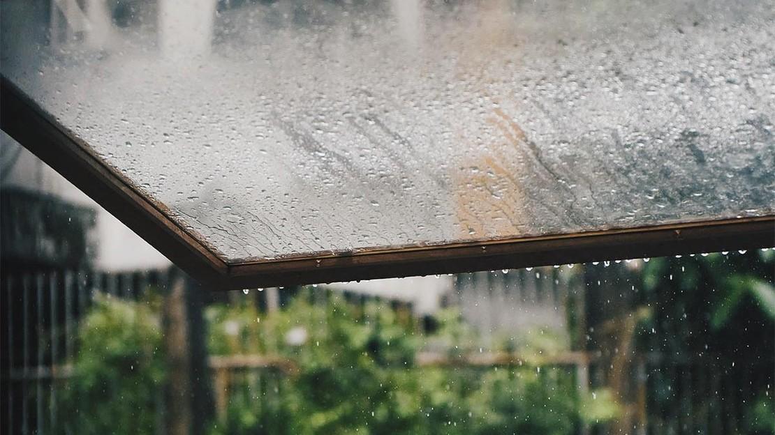Fotografie eines Glasdachs, von dem Regen abperlt.