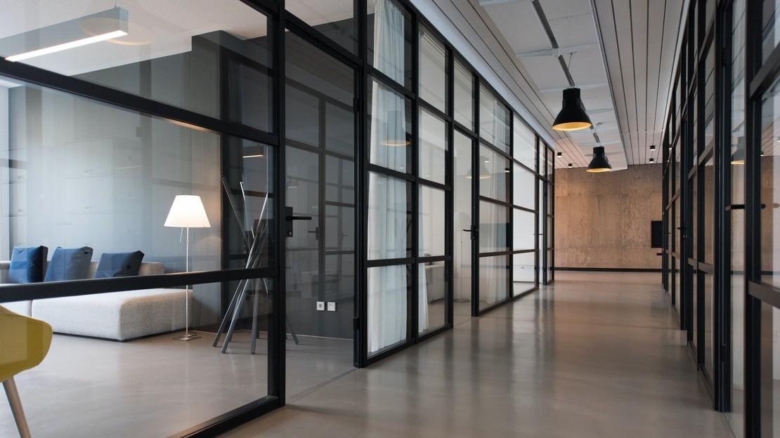 Fotografie eines modernen Büroflurs mit gläsernen Trennwänden.