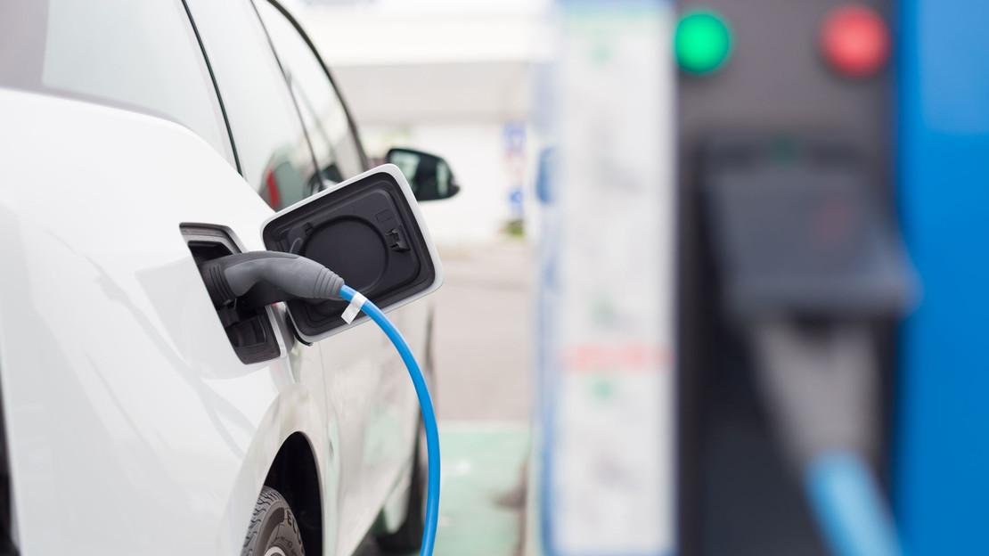 Fotografie eines an eine Stromladesäule angeschlossenen Autos.