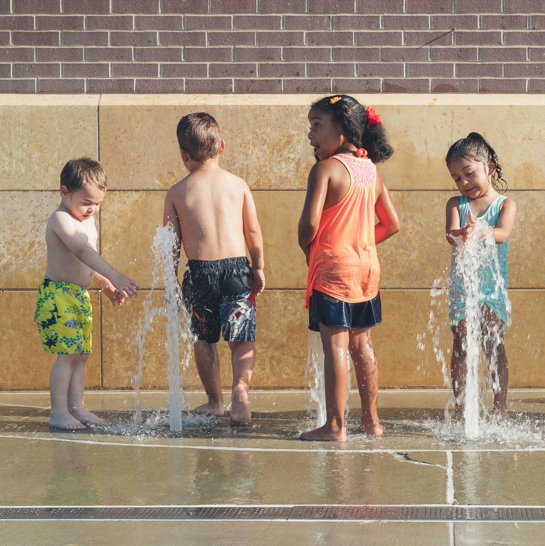Ein Gruppe von Kindern spielt an einem Springbrunnen.