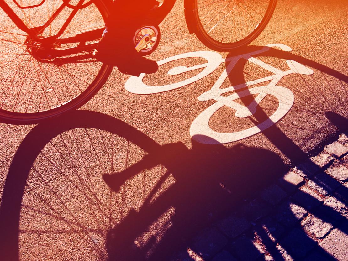 Fotografie eines Radwegs mit Schatten eines Radfahrers.